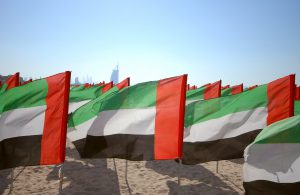 Close up of flags United Arab Emirates for the anniversary celebration on the beach. UAE Natoinal day. Emirates Flag. UAE celebrates National Day on 2nd December every year.